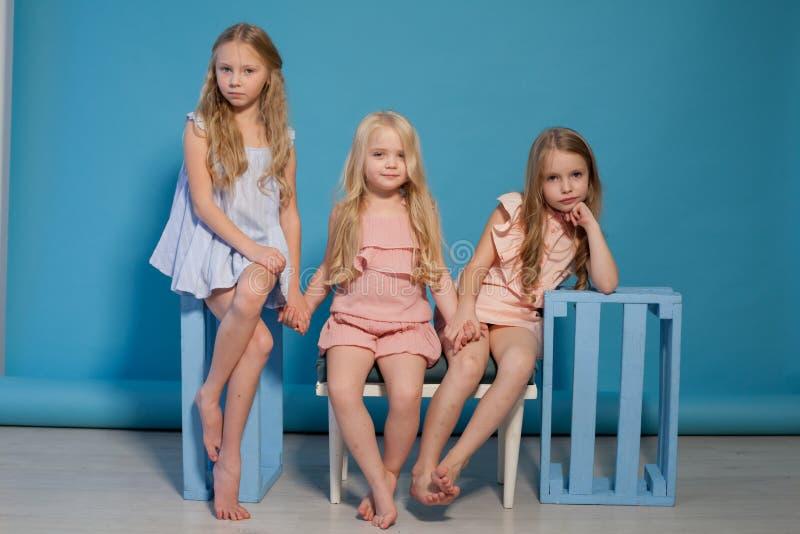Ritratto biondo della sorella di tre amiche delle bambine alla moda immagine stock