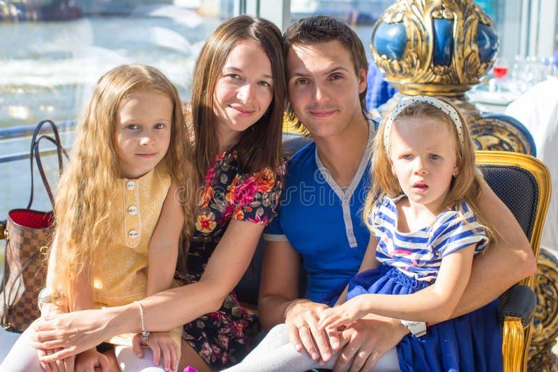 Ritratto che incanta bella famiglia di quattro in ristorante immagine stock