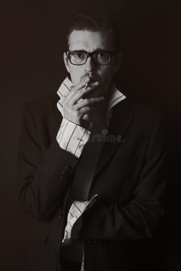 Ritratto classico del giovane in vetri con la sigaretta fotografia stock