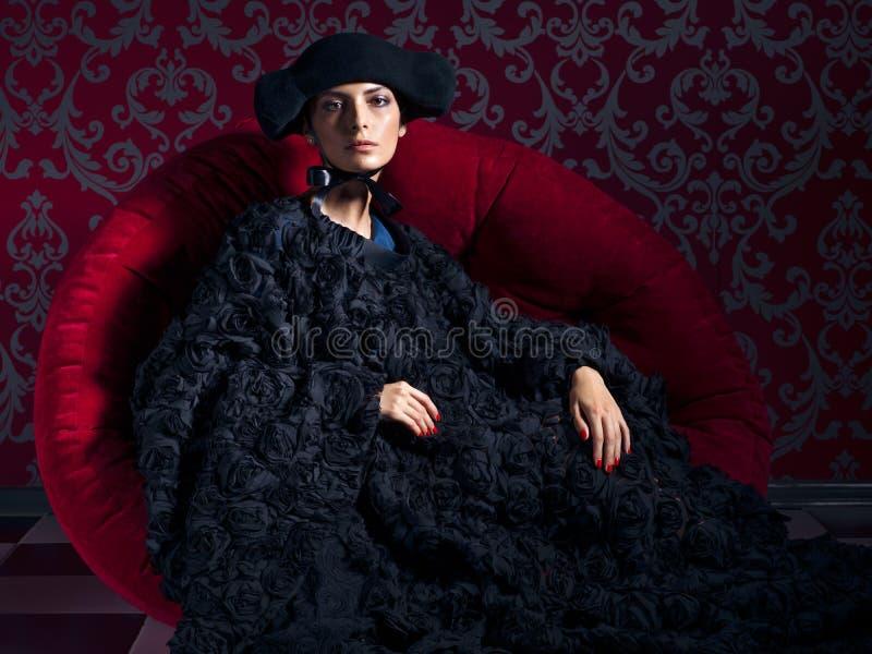 Ritratto classico della donna che porta il vestito black hat dall'estremità che si siede sul sofà rosso immagini stock libere da diritti