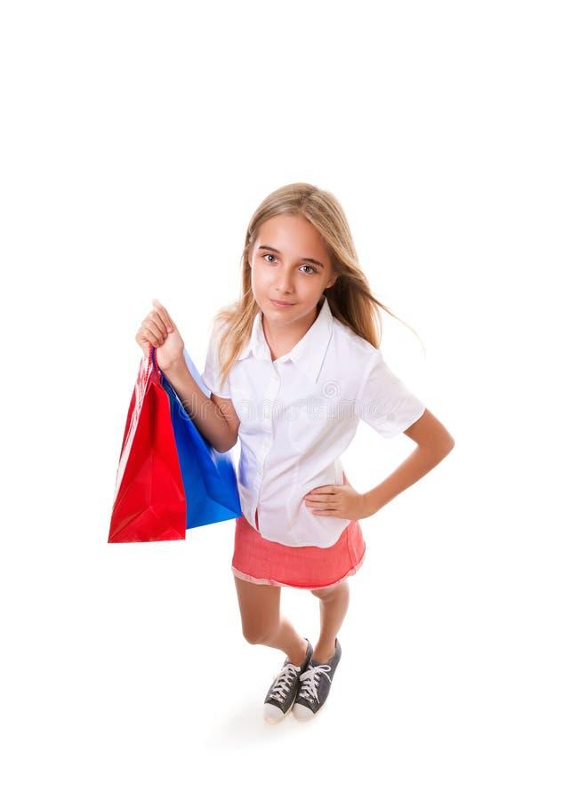 Ritratto completo del corpo dell'angolo alto di divertimento dell'adolescente adorabile con i sacchetti della spesa, iolated fotografia stock libera da diritti