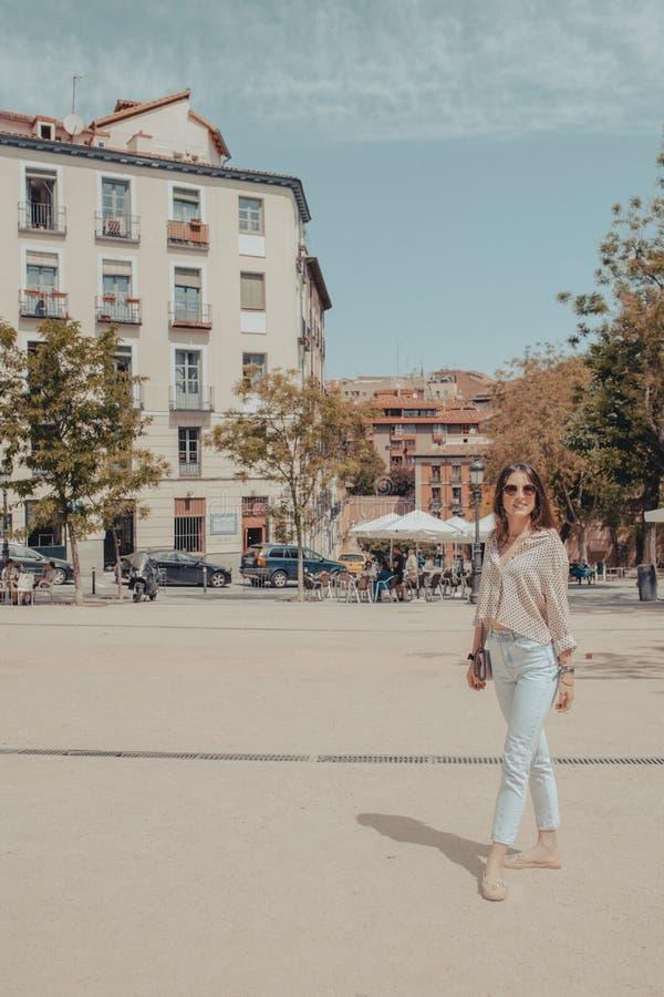 Ritratto completo del corpo di bella giovane donna turistica che visita la città di Madrid, Spagna Ragazza che propone sulla via immagini stock