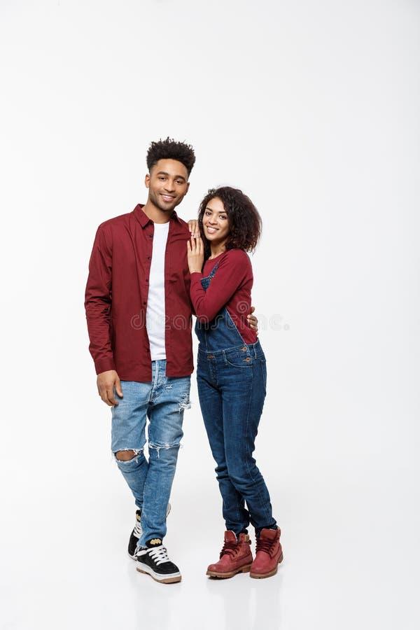 Ritratto completo del corpo di giovane afroamericano che abbraccia le coppie, con il sorriso Datazione, flirtante, amanti, studio fotografia stock libera da diritti