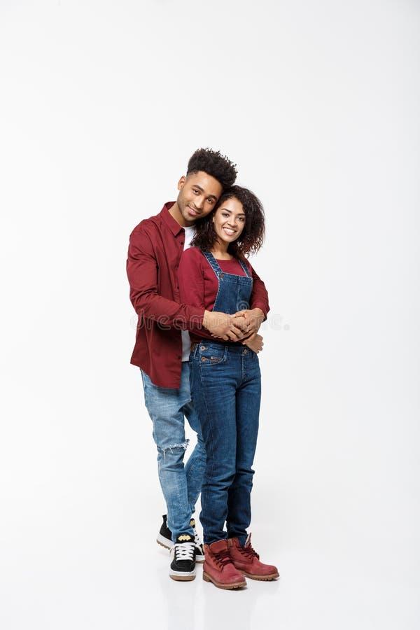 Ritratto completo del corpo di giovane afroamericano che abbraccia le coppie, con il sorriso Datazione, flirtante, amanti, studio fotografia stock