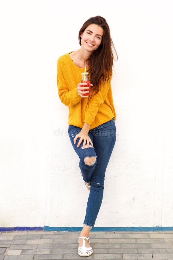 Ritratto completo della giovane donna che sta all'aperto con il succo fotografia stock
