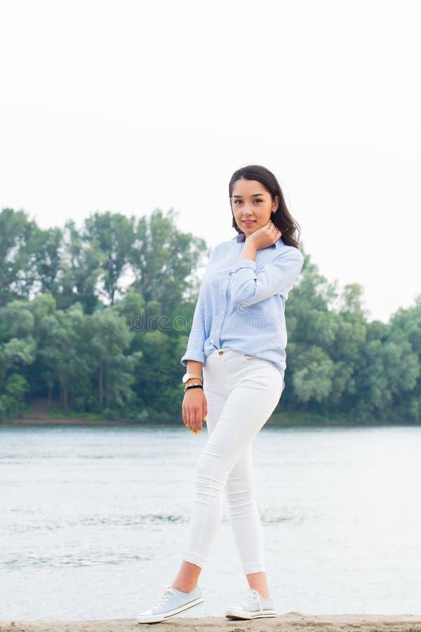 Ritratto completo di altezza di bella donna castana sul lungofiume Sguardo sorridente della ragazza fotografia stock