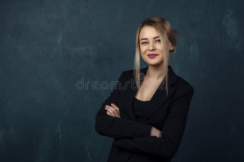 Ritratto con i lotti dei dettagli, bella donna sorridente del primo piano in vestito nero contro un fondo strutturale blu della p fotografia stock