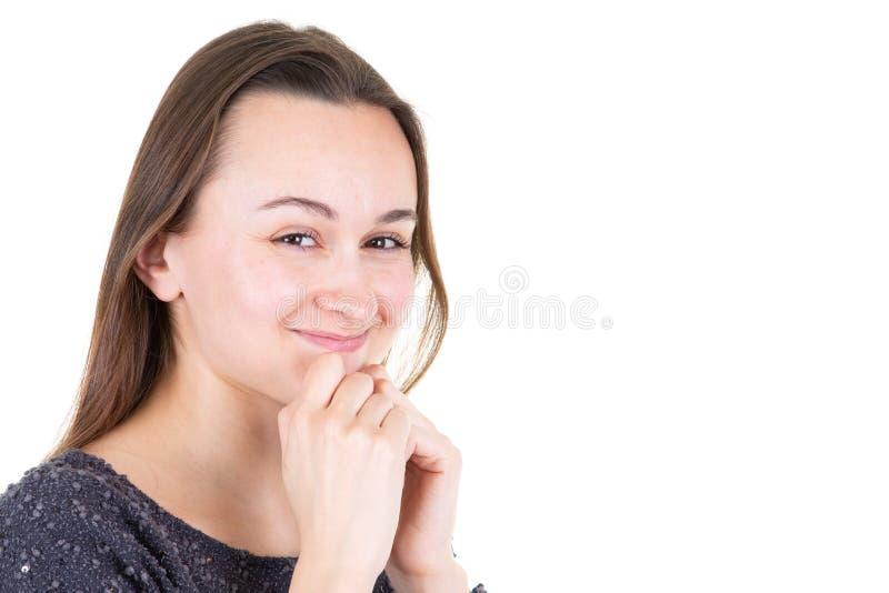 Ritratto con lo spazio della copia della ragazza graziosa che tiene le dita sul mento che esamina macchina fotografica che contro fotografia stock