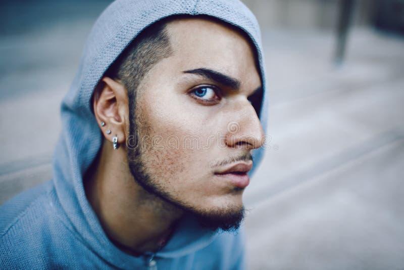 Ritratto concettuale di arte di bello uomo castana di Medio Oriente con gli occhi azzurri, perforante nella maglia con cappuccio  fotografie stock libere da diritti