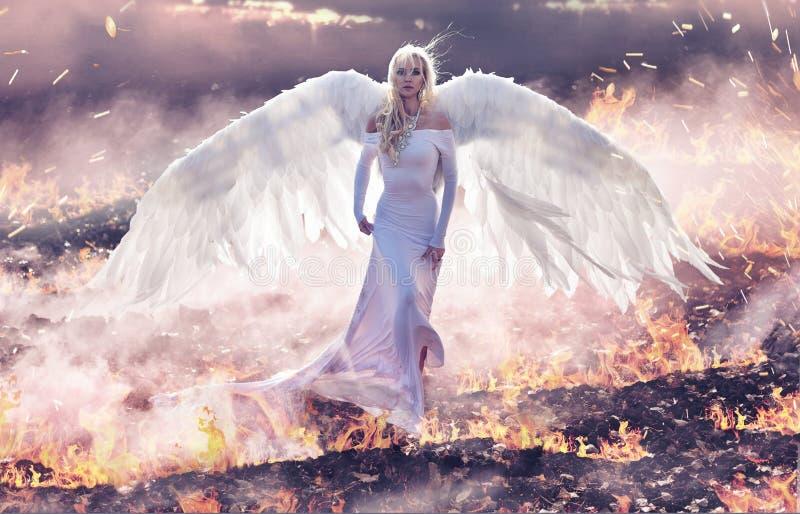 Ritratto concettuale di un angelo che cammina sulle fiamme dell'inferno fotografie stock