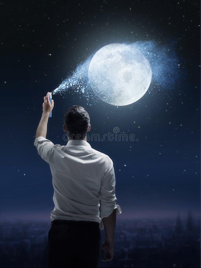 Ritratto concettuale di un uomo che spruzza una luna fotografia stock libera da diritti