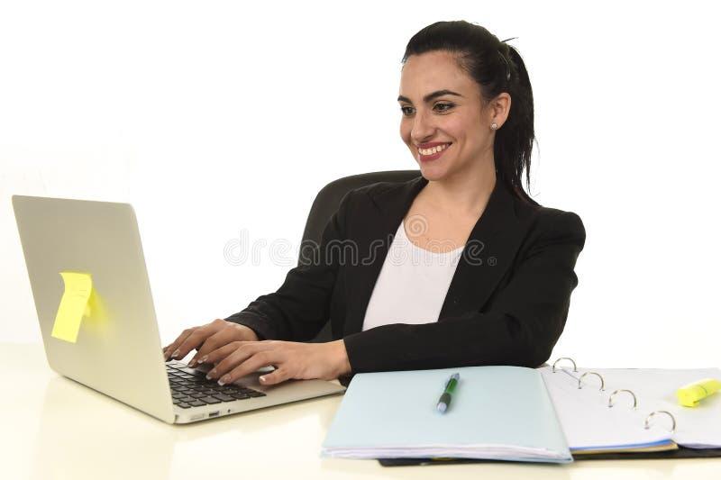 Ritratto corporativo di giovane bello lavoro ispanico della donna felice e rilassato all'ufficio del computer portatile fotografie stock libere da diritti