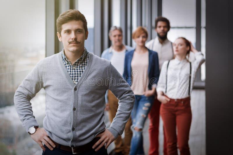 Ritratto corporativo di giovane uomo d'affari dei pantaloni a vita bassa con i suoi colleghi nel fondo fotografia stock
