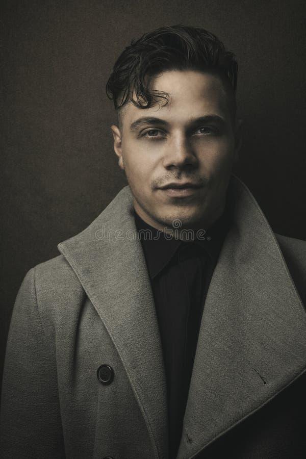Ritratto d'annata e retro dell'uomo illuminato in cappotto grigio con fondo marrone Giovane tipo con la vecchia acconciatura Ritr fotografia stock