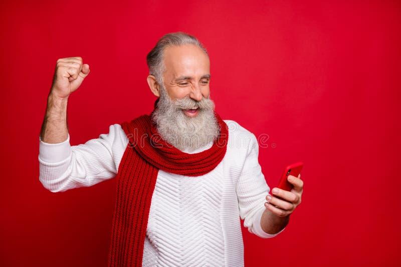 Ritratto da vicino del suo simpatico allegro allegro e felice uomo dai capelli grigi che tiene per mano con il cellulare fotografia stock