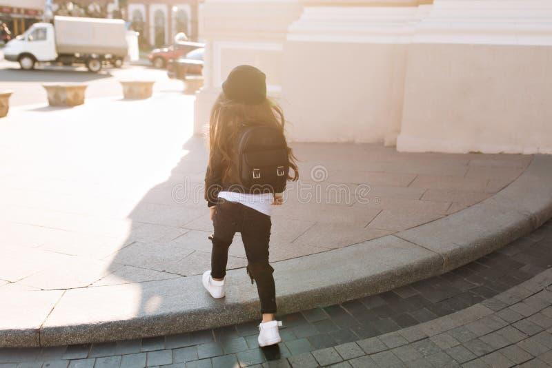 Ritratto dalla parte posteriore della bambina in cappello d'avanguardia e jeans neri che cammina sulla via nel giorno soleggiato  immagine stock libera da diritti