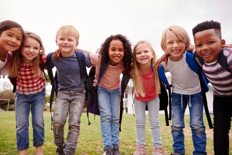 Ritratto degli allievi emozionanti della scuola elementare sul campo da gioco a tempo della rottura fotografia stock