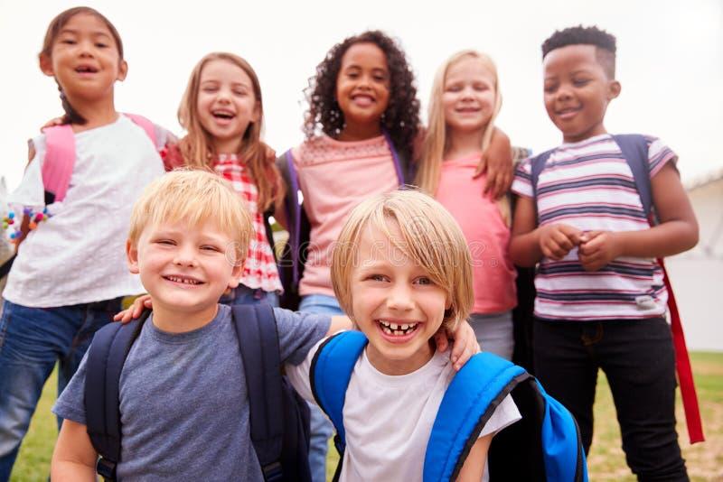 Ritratto degli allievi emozionanti della scuola elementare sul campo da gioco a tempo della rottura fotografie stock