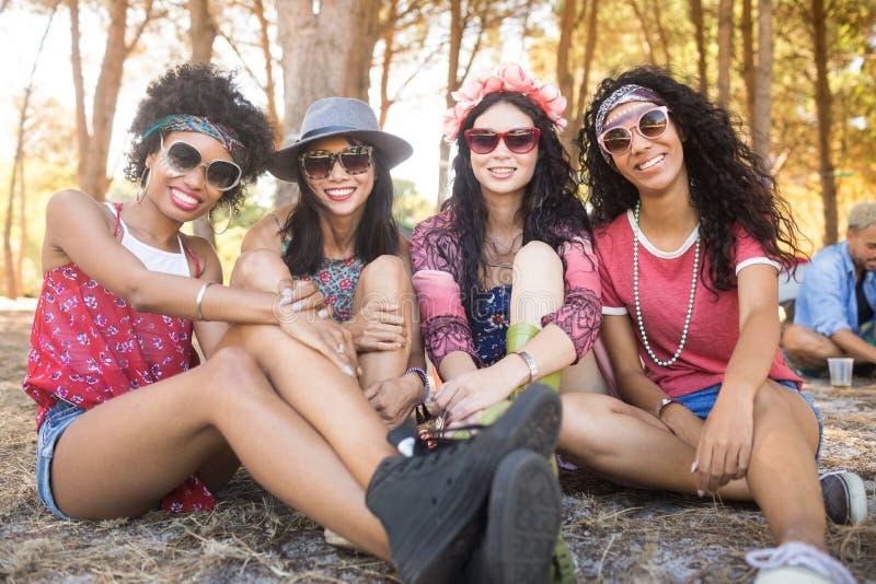 Ritratto degli amici femminili felici che si siedono insieme al campeggio immagine stock libera da diritti