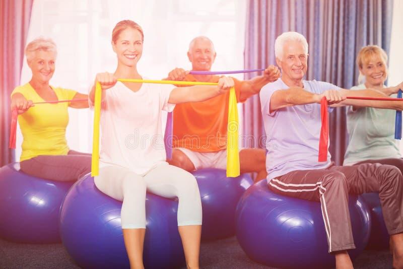 Ritratto degli anziani che usando la palla di esercizio ed allungando le bande immagini stock