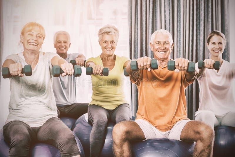 Ritratto degli anziani che usando la palla ed i pesi di esercizio immagini stock libere da diritti