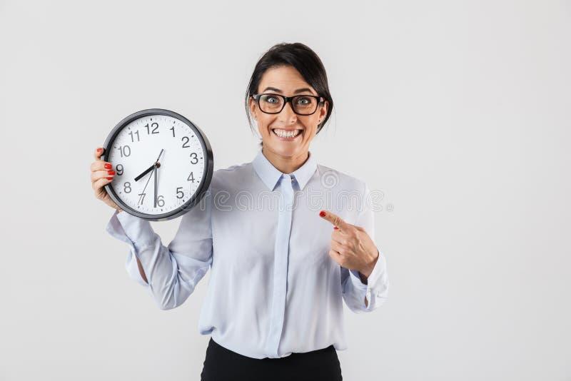 Ritratto degli occhiali d'uso sorridenti della donna di affari che tengono orologio rotondo nell'ufficio, isolato sopra fondo bia fotografie stock