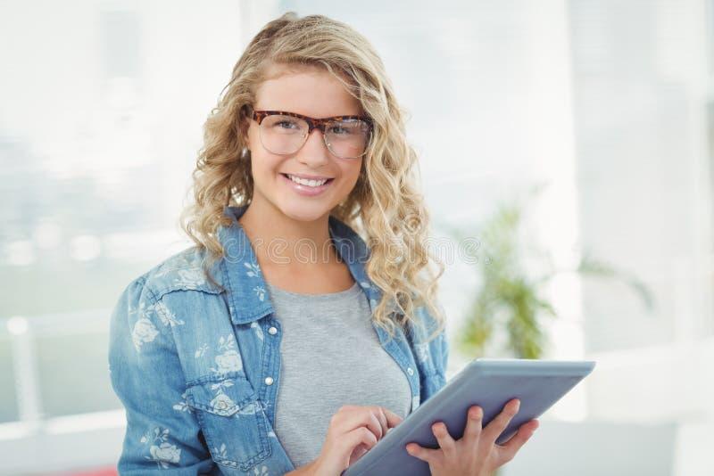Ritratto degli occhiali d'uso sorridenti della donna mentre per mezzo della compressa digitale immagine stock