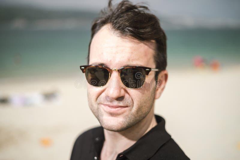 Ritratto degli occhiali da sole da portare del giovane uomo bello fotografia stock libera da diritti