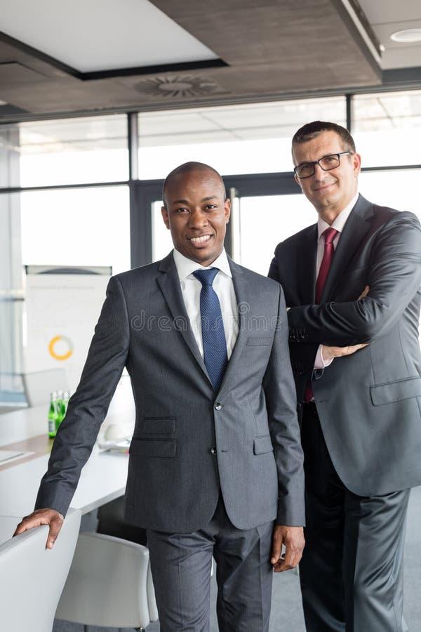 Ritratto degli uomini d'affari sicuri che stanno insieme nell'ufficio fotografia stock libera da diritti