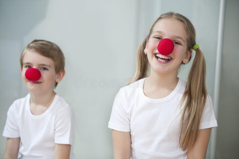 Ritratto dei bambini che indossano i nasi del pagliaccio fotografia stock libera da diritti