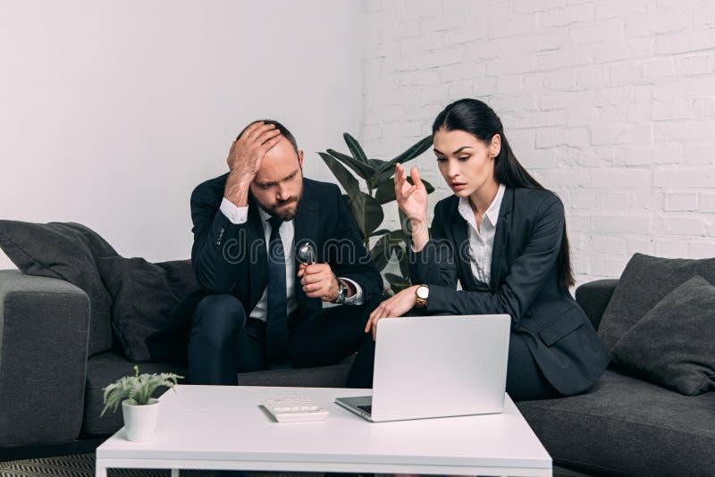 ritratto dei colleghi sollecitati di affari che si siedono sul sofà al tavolino da salotto con il computer portatile fotografia stock libera da diritti