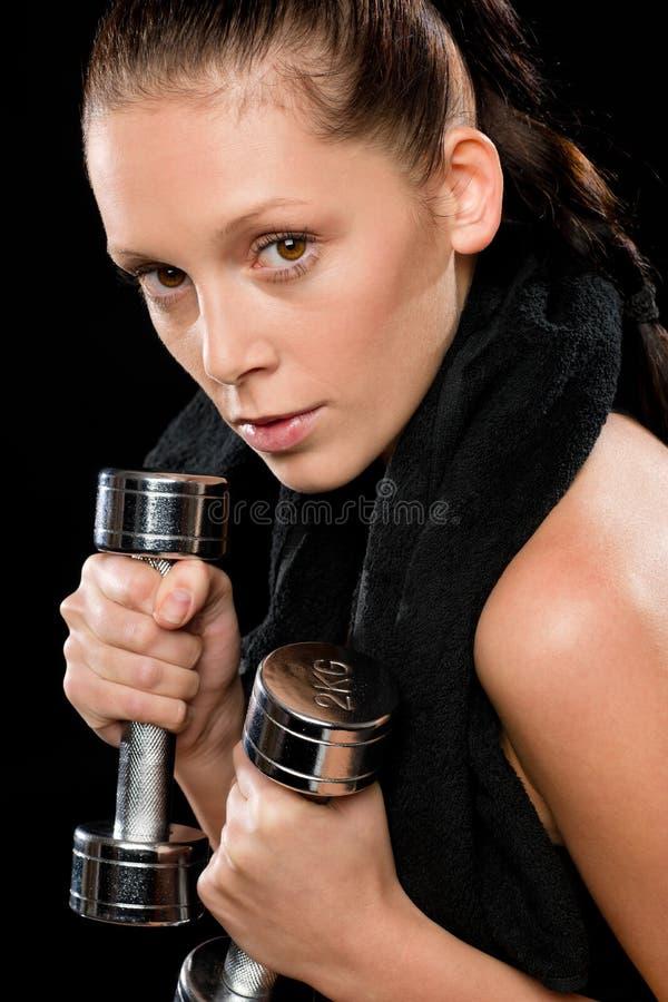 Ritratto dei dumbbells di sollevamento della giovane donna graziosa fotografia stock libera da diritti