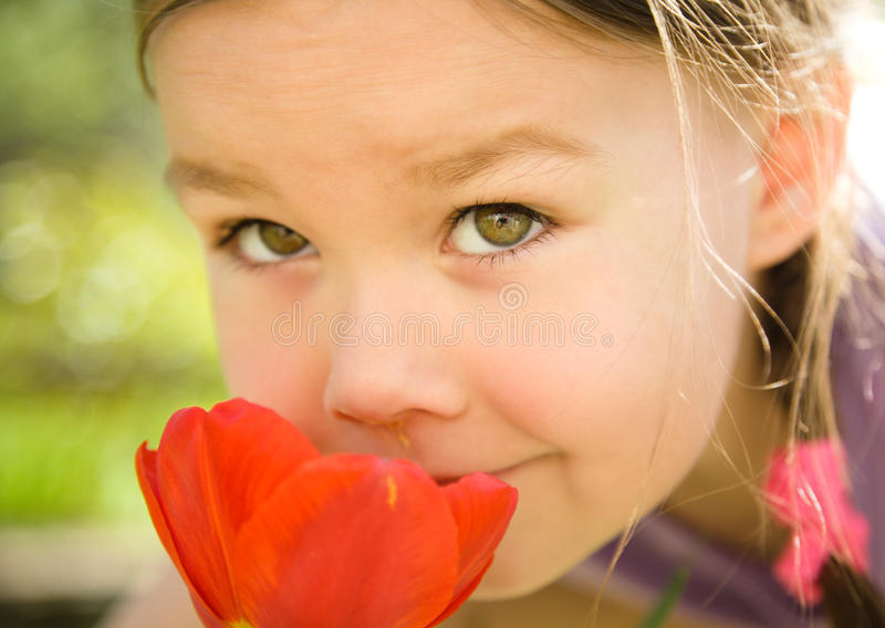 Ritratto dei fiori sententi l'odore della bambina sveglia fotografie stock