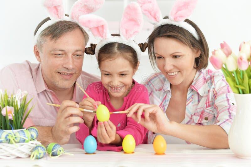 Ritratto dei genitori con le uova di coloritura della piccola figlia sveglia immagine stock libera da diritti
