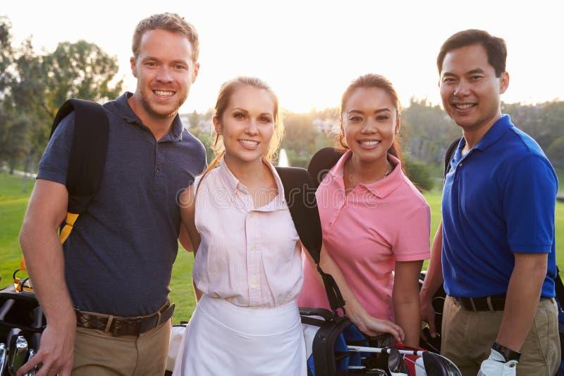 Ritratto dei giocatori di golf che camminano lungo le borse di golf di trasporto del tratto navigabile fotografie stock libere da diritti