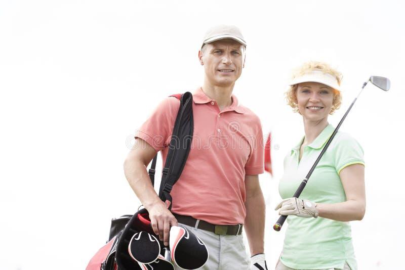 Ritratto dei giocatori di golf maschii e femminili felici che stanno contro il chiaro cielo fotografia stock