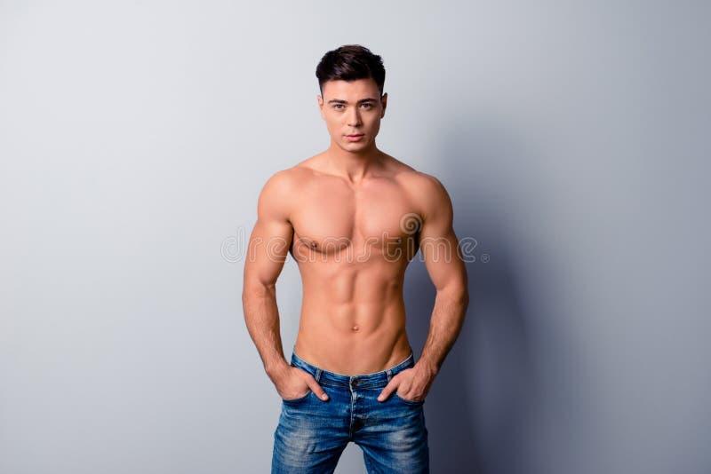 Ritratto dei jeans d'uso del forte uomo sportivo sicuro bello, fotografia stock libera da diritti