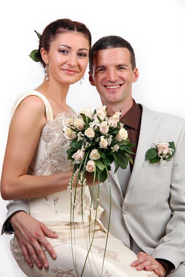 Ritratto dei newlyweds felici su priorità bassa bianca fotografie stock libere da diritti