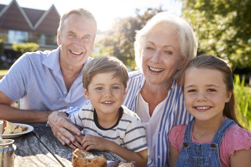 Ritratto dei nonni con i nipoti che godono dello spuntino all'aperto di estate al caffè immagini stock libere da diritti