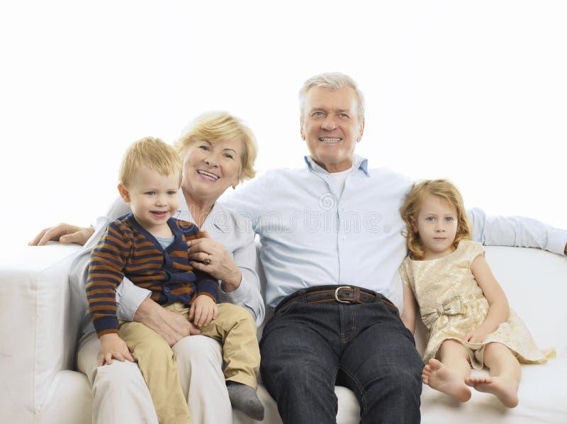 Ritratto dei nonni e dei nipoti sul sofà fotografie stock