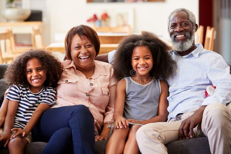 Ritratto dei nonni sorridenti con i nipoti che si siedono su Sofa At Home Relaxing Together fotografia stock