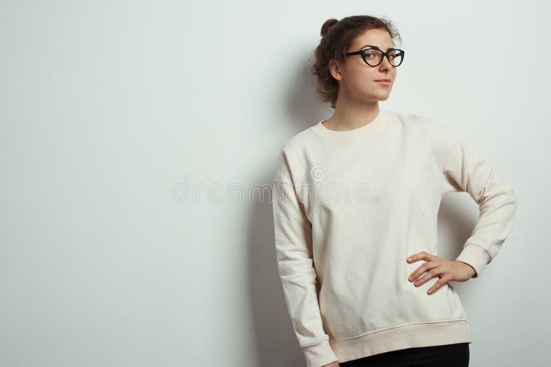Ritratto dei pantaloni a vita bassa affascinanti della donna che indossano i vetri in bianco dell'occhio e del maglione Fondo vuo fotografia stock libera da diritti