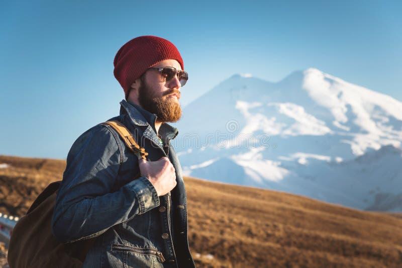 Ritratto dei pantaloni a vita bassa alla moda premurosi con una barba in occhiali da sole ed in un cappello con uno zaino sui pre fotografie stock libere da diritti
