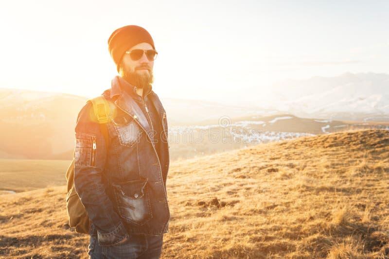 Ritratto dei pantaloni a vita bassa alla moda premurosi con una barba in occhiali da sole ed in un cappello con uno zaino sui pre immagini stock libere da diritti
