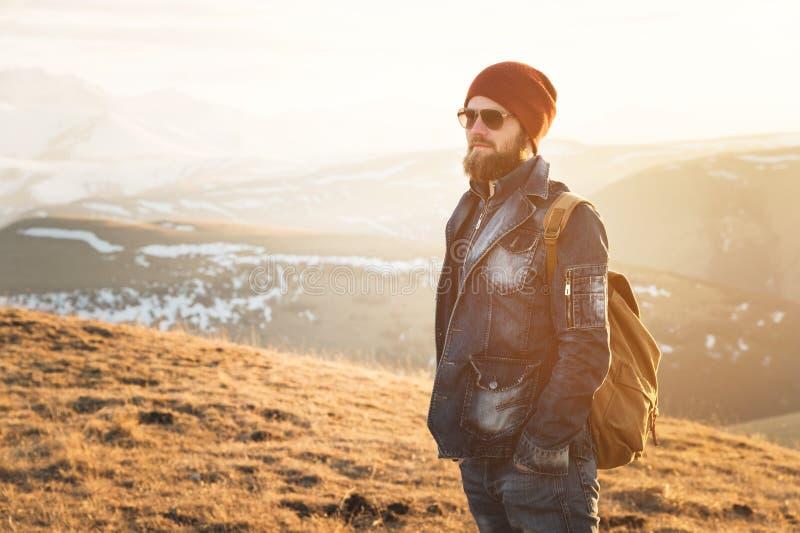 Ritratto dei pantaloni a vita bassa alla moda premurosi con una barba in occhiali da sole ed in un cappello con uno zaino sui pre immagine stock