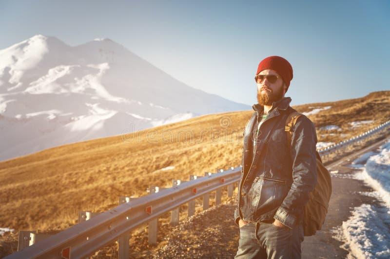 Ritratto dei pantaloni a vita bassa alla moda premurosi con una barba in occhiali da sole ed in un cappello con uno zaino sui pre fotografie stock