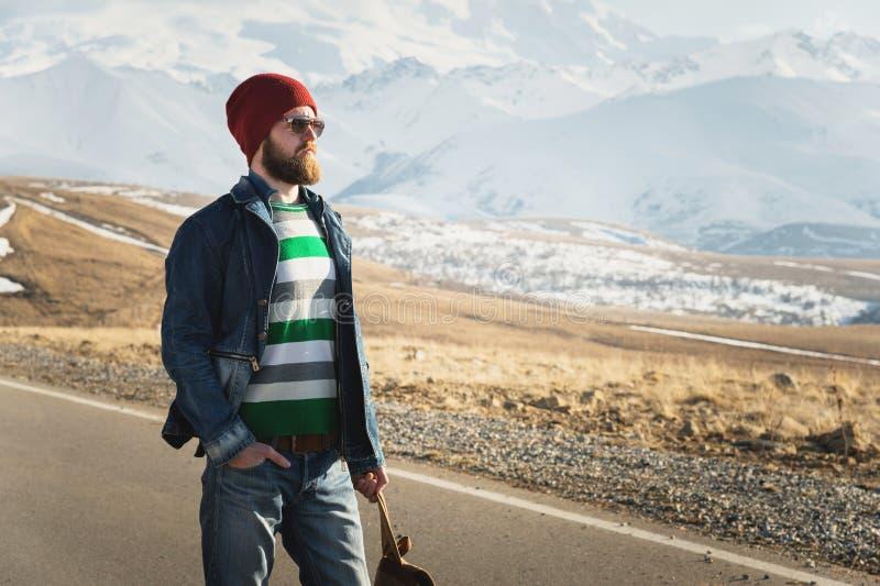 Ritratto dei pantaloni a vita bassa alla moda premurosi con una barba in occhiali da sole ed in un cappello con uno zaino sui pre fotografia stock