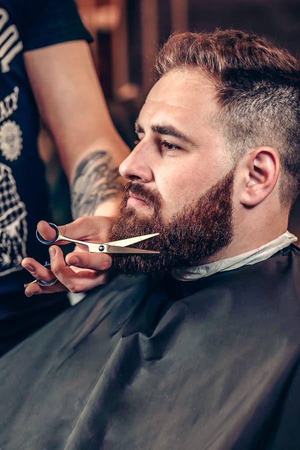 Ritratto dei pantaloni a vita bassa barbuti dell'uomo in un parrucchiere immagini stock