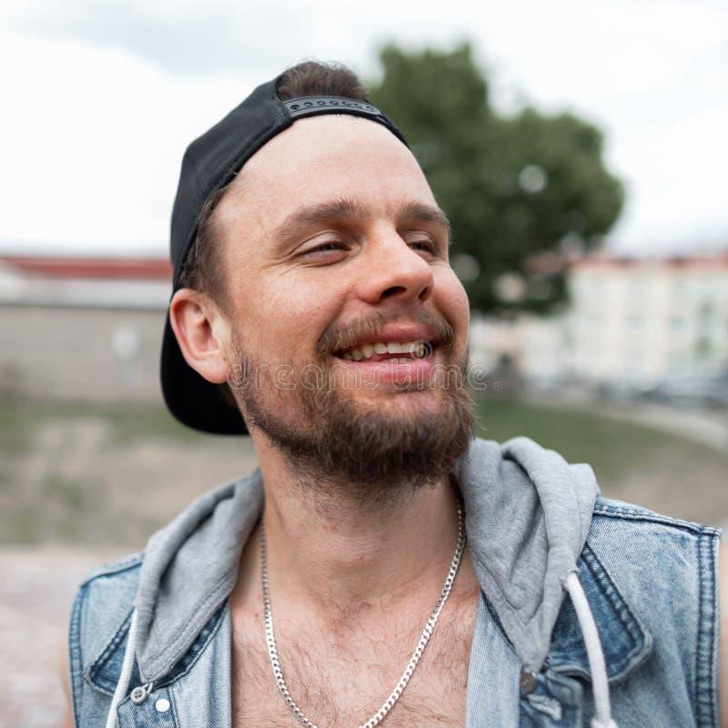 Ritratto dei pantaloni a vita bassa felici del giovane con una barba con un sorriso sveglio in un cappuccio alla moda nero in una immagini stock