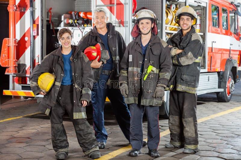 Ritratto dei pompieri sicuri che stanno contro il camion immagine stock